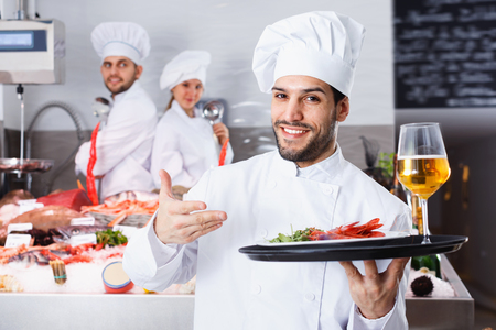 Portrait of professional glad cheerful  smiling chef with serving tray offering seafood in fish restaurant