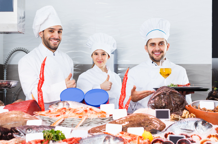 Team of fish restaurant chefs standing behind icy showcase, offering fresh seafood