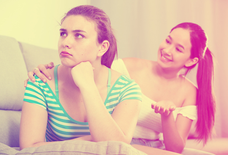 Teenage girl asking for forgiveness from her offended female friend sitting sofa