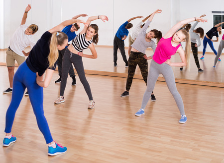 happy russian teenage boys and girls with trainer stretching in dance hall