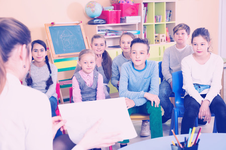 Portrait of diligent friendly  positive  pupils listening teacher at lesson in elementary school