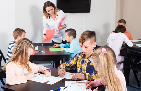 Group of children in elementary age drawing at classroom in school Stock Photo