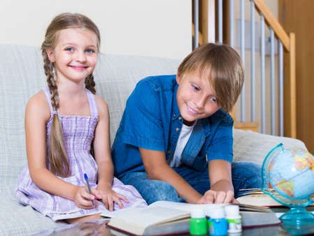 Teenage boy and younger sister learning with books indoors