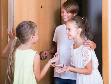 Two little girls with teenage boy meeting in doorway and laughing