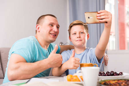 Guy with his father are resting and taking selfie by phone at the home.