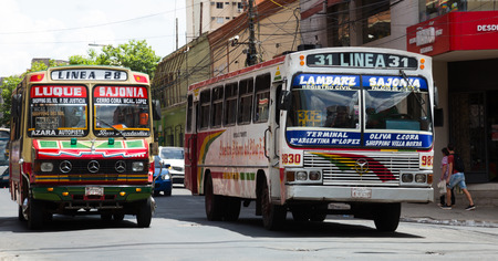 ASUNCION, PARAGUAY – FEBRUARY 15, 2017:  Lively urban traffic on city streets with colorful buses. Asuncion, Paraguay