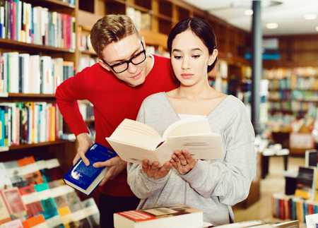 Cheerful positive smiling girl reading book in bookstore while guy looking at her book over her shoulder