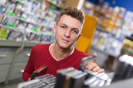 Ordinary man looking for interesting movies on shelves of CD shop