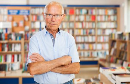 Portrait of confident senior man standing in interior of modern bookstore