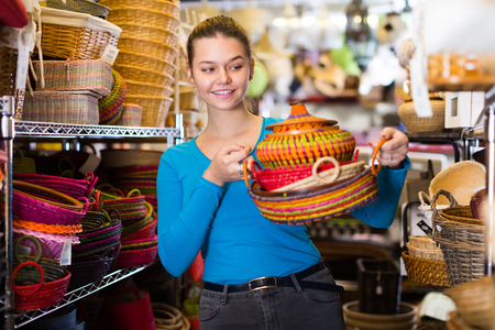 girl customer choosing multicolor wicker basket in decor items store