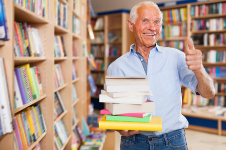 Portrait of positive intelligent older man standing in library with pile of books in hands