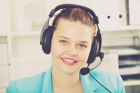 Portrait of dispatcher female which is talking with client in the office.