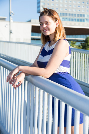 Portrait of young stylish girl posing on city bridge in summer day Stock Photo