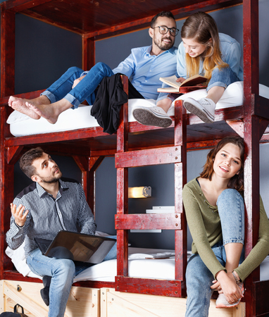Portrait of young positive glad travelers communicating while resting in modern cozy hostel bedroom Stock Photo
