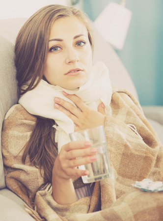Young woman catching cold taking medication under blanket on sofa