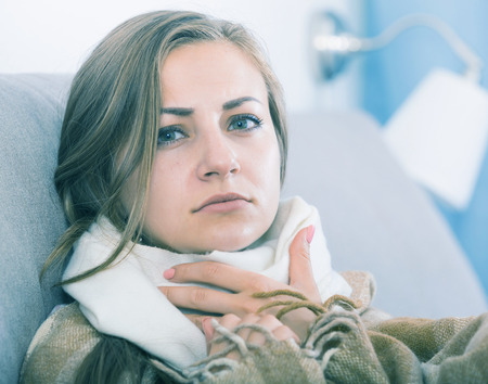 Young woman catching cold, wrapping in blanket Reklamní fotografie