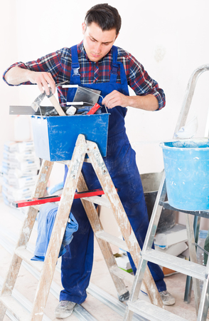 Young concentrated builder handyman choosing necessary tool in toolbox Stock Photo