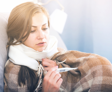 Ill girl with flu virus lying on couch measuring temperature with thermometer