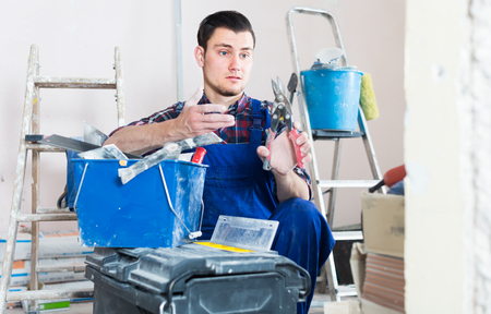 Young professional builder handyman choosing necessary tool in toolbox