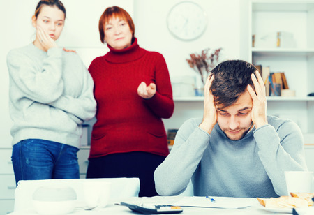 Frustrated young man looking at papers on background with discontented wife and her mother