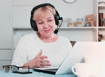 Happy mature woman in headphones with microphone communicating via internet