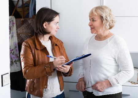 La donna matura risponde alle domande dell'intervistatore a casa Archivio Fotografico