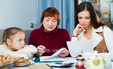 Upset grandmother, mother and daughter attentively reading documents while sitting at home Фото со стока