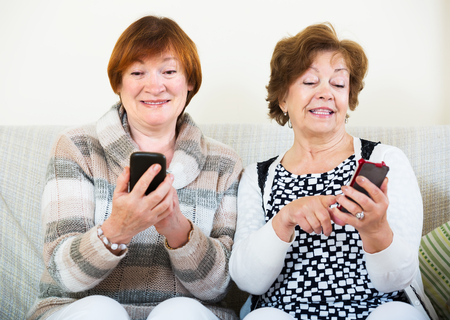 Smiling mature women sitting with mobile phones in living room