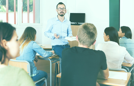serious adult teacher is giving lecture for students with book in the class. Stock Photo