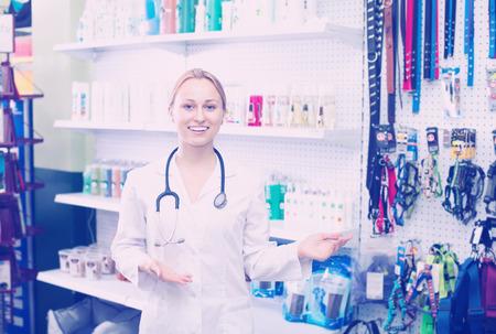 Smiling female vet advising on pet cosmetics in pet store
