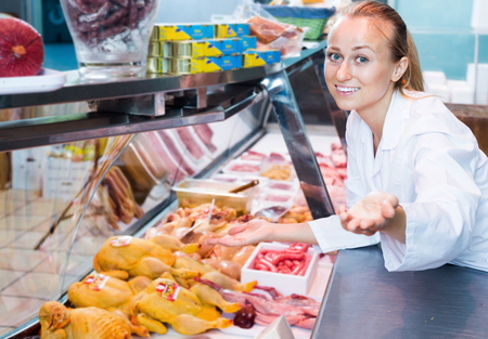 Smiling female  working in meat shop in delicatessen section