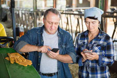 Mature man and woman farmers using phones, standing near tractor on farm