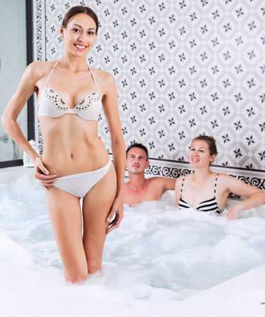 Healthy lifestyle - three people relaxing enjoying jacuzzi hot tub bubble bath in spa complex