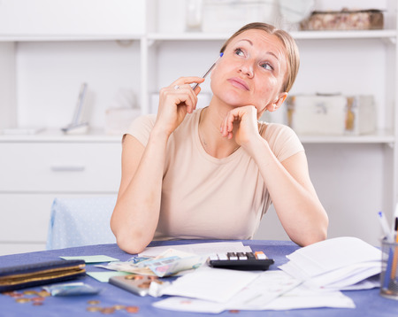 Frustrated woman facing financials troubles at table with bills, money and calculator Stock Photo