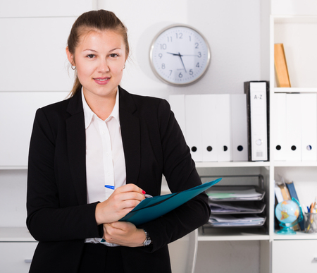Office manager woman in black suit is signing agreement papers of financial nature at office.