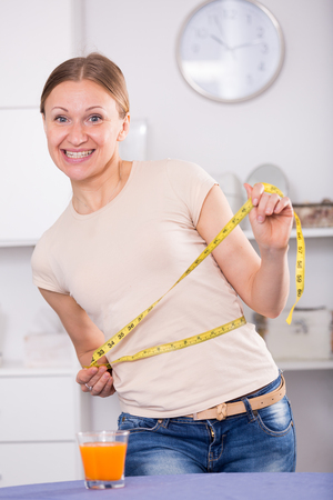 Young woman feeling happy measuring her waist at home