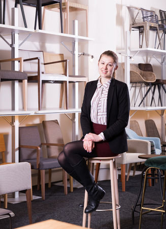 Portrait of young attractive salesgirl sitting on chairs for sale in furniture shop