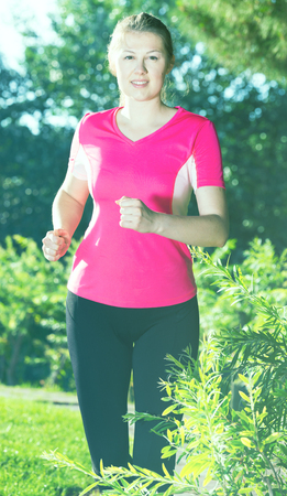Young girl in pink T-shirt is running around in the park. Imagens