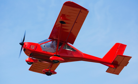 Sport airplane soaring in blue sky in sunny day