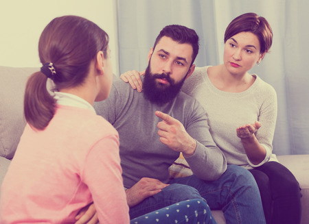 Father and mother telling off their daughter for disobedience Stock Photo