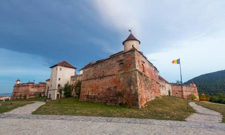 Twilight landscape with massive medieval Brasov Fortress, Romania Foto de archivo