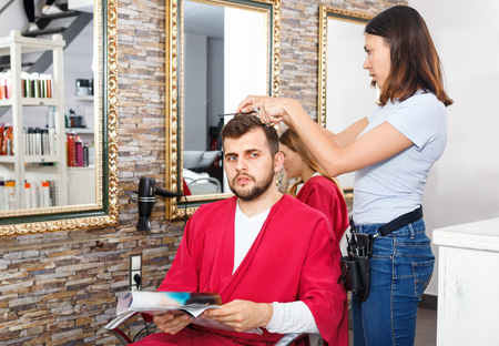 Cheerful glad  positive  woman professional hairdresser cut male's hair in hairdressing salon