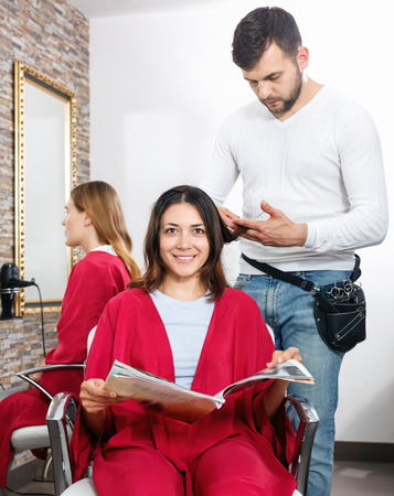 Positive glad cheerful smiling  man hairdresser cuts hair of young woman with magazine at salon