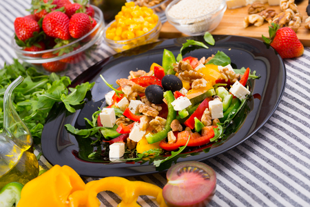 Salad with arugula, olives, Feta cheese, corn and walnut and its ingredients in the kitchen.