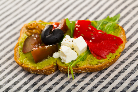 Delicious sandwich with guacamole, fresh tomatoes, sweet pepper and feta cheese on striped textile background 版權商用圖片