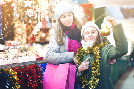 Smiling girl with woman are preparing for a Christmas and choosing a balls on the tree outdoor. Focus on child Stock Photo