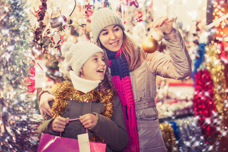 Young girl and her mother are choosing decorations for Christmas tree in the market outdoor.