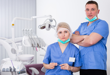 Portrait of two confident professional dentists in modern dental office
