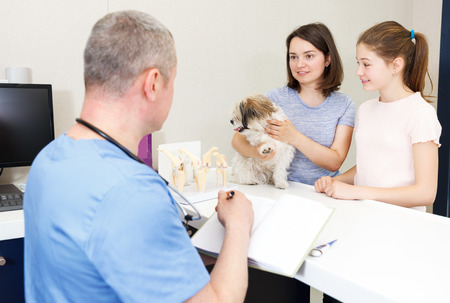 Worried young mother and daughter with their little puppy visiting veterinarian clinic Stock Photo