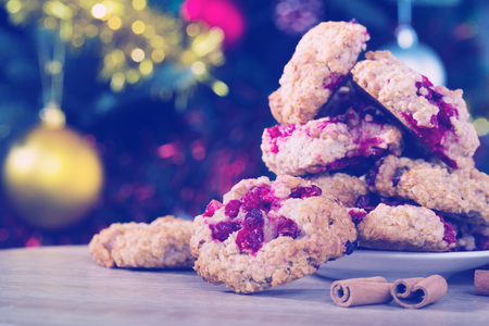 Oatmeal biscuits in saucer with cinnamon on wooden surface on blurry background with Christmas tree Фото со стока